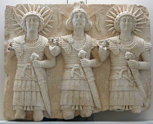 An ancient sculpture depicting Baalshamin (center) along with his Lunar and Solar counterparts.